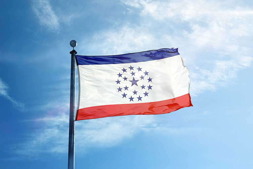 The Mississippi State flag (proposed by Knol Aust) flies high on a flag pole waving in the wind.