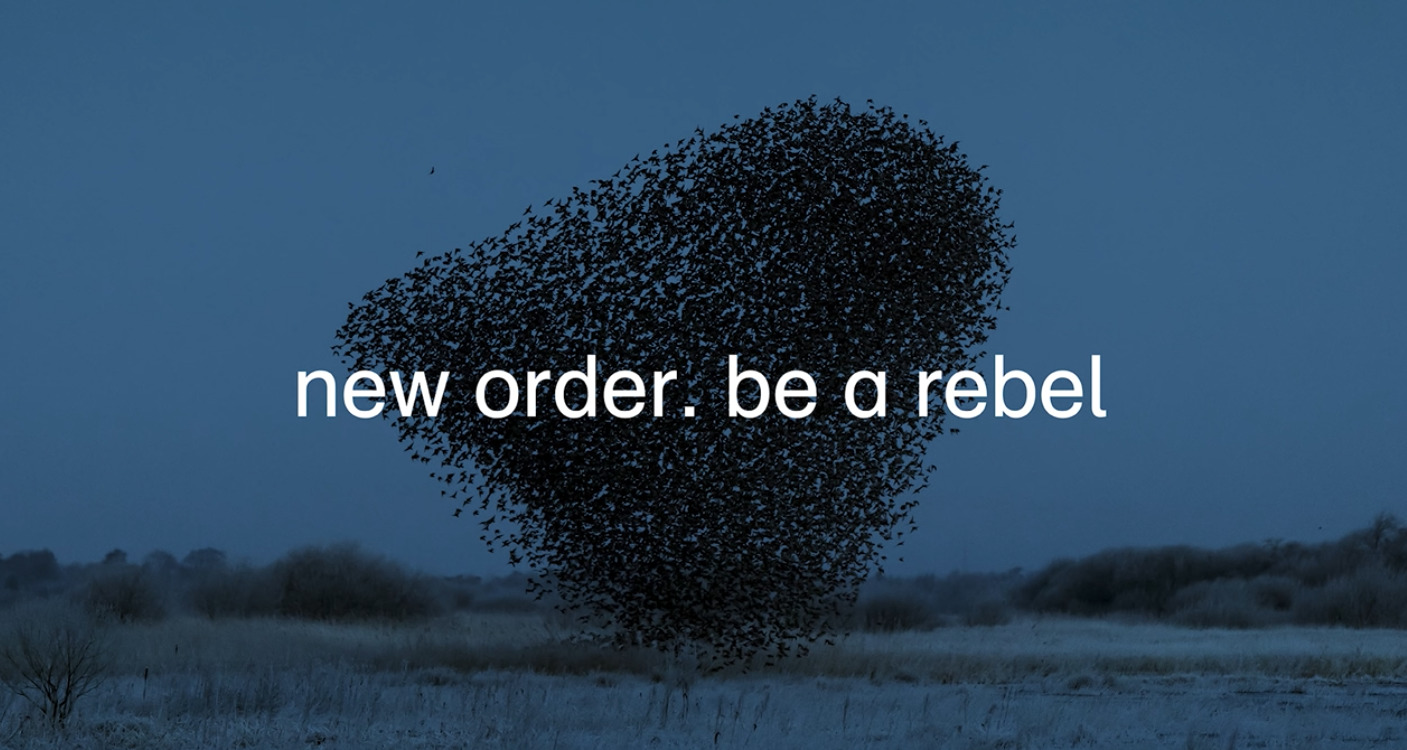 Artwork for New Order's single Be a Rebel includes a deep blue image of a large flock black birds swirling.